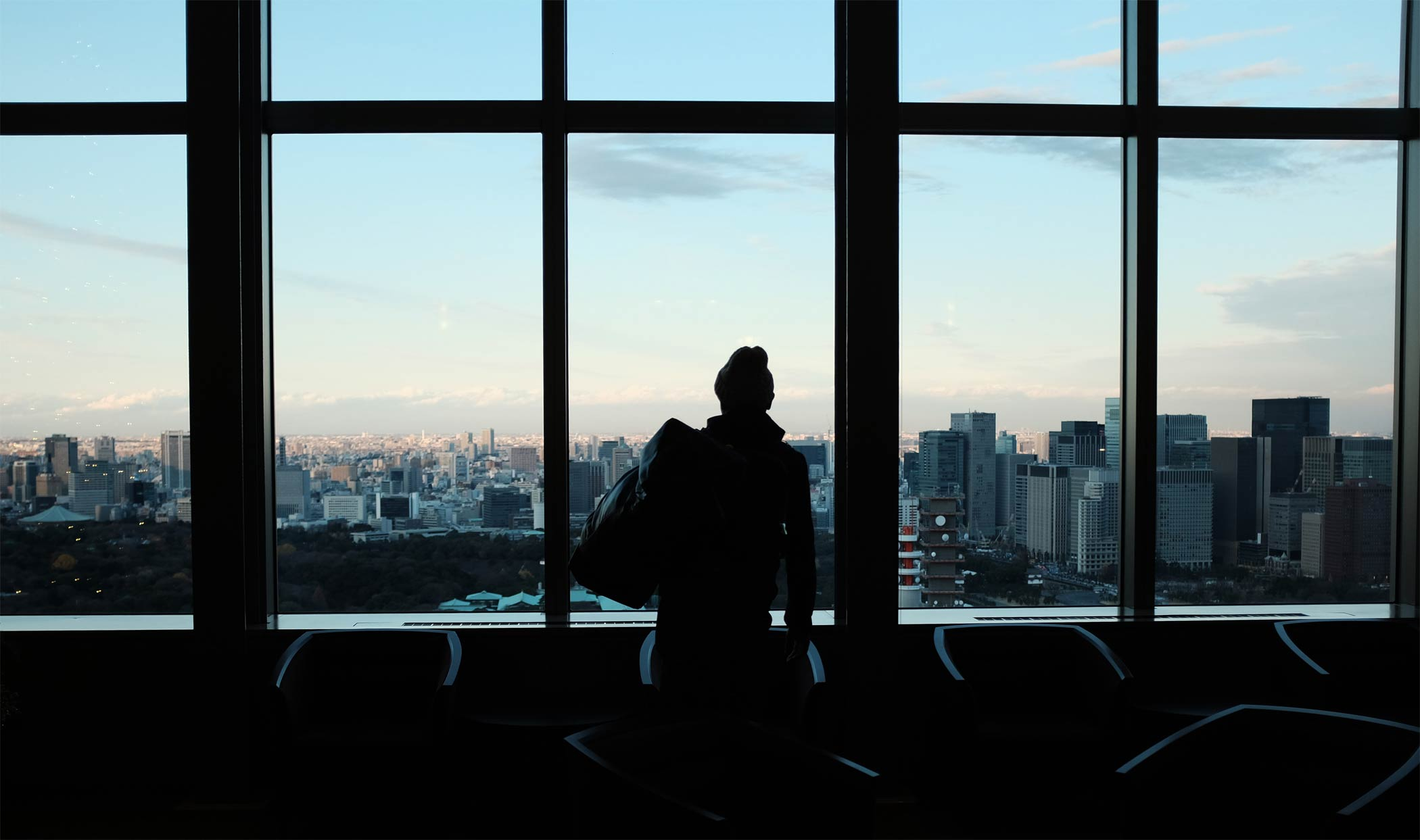 A woman in a high rise business building looking out of the large window to Washington