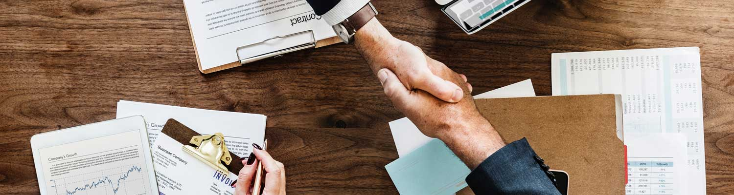 two business men shaking hands over documents
