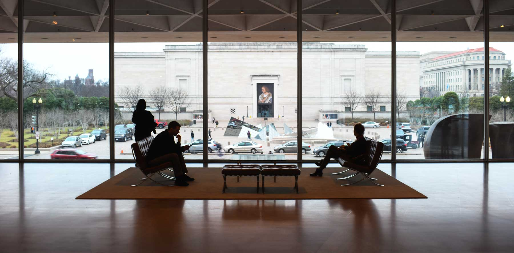 Two business men sitting in a grand lobby over looking Washington DC