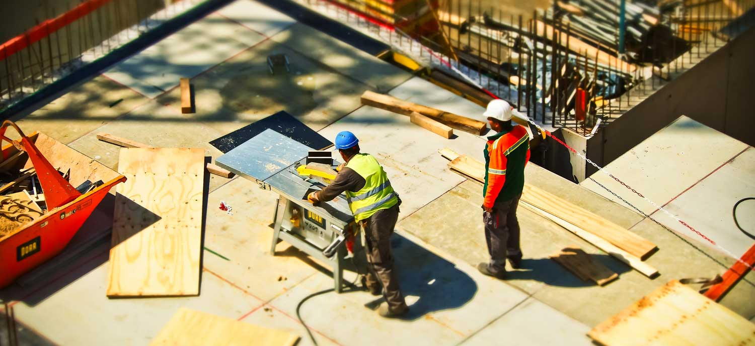 Two construction workers working outside in hard hats